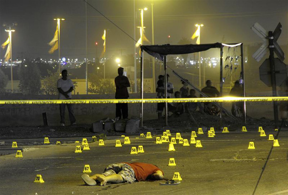 A man lies dead among evidence markers at a crime scene in the border city of Ciudad Juarez