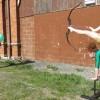 【衝撃動画】逆立ちして足で弓を弾き風船に命中させる凄技を見せてくれるレオタードの女の子。