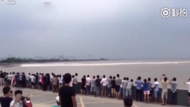 中国・銭塘江の大逆流を待ち構える観光客たちの画像
