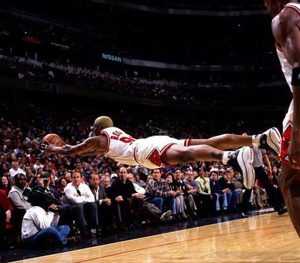 ボールをダイビングキャッチしてるバスケットボール選手