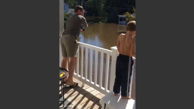 家の周りが浸水したので釣りをする親子