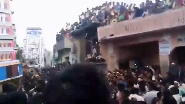 建物の上からお祭りを見学する人たち