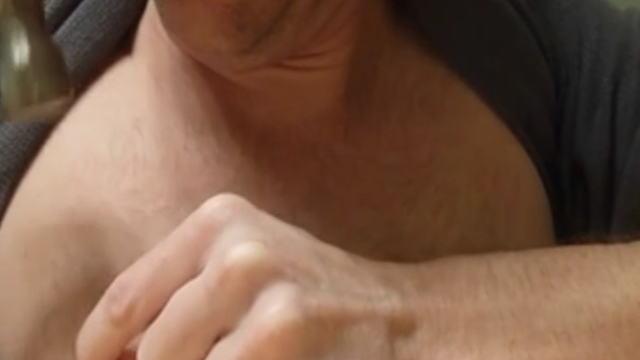乳首に釘を刺し金槌で板に打ち付ける男性