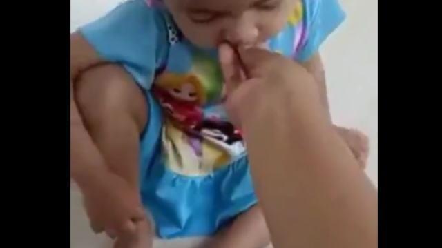 幼児にミミズを食べさせる母親